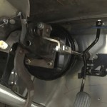 Hidden brake booster and clutch linkage